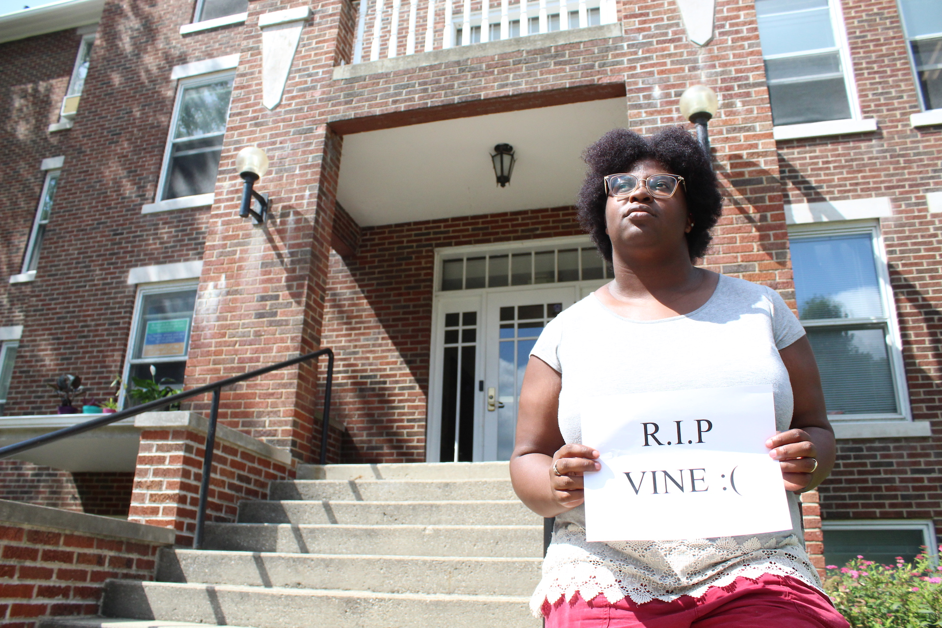 """A student stands outside Kulp Hall with a sign reading """"R.I.P. VINE"""""""