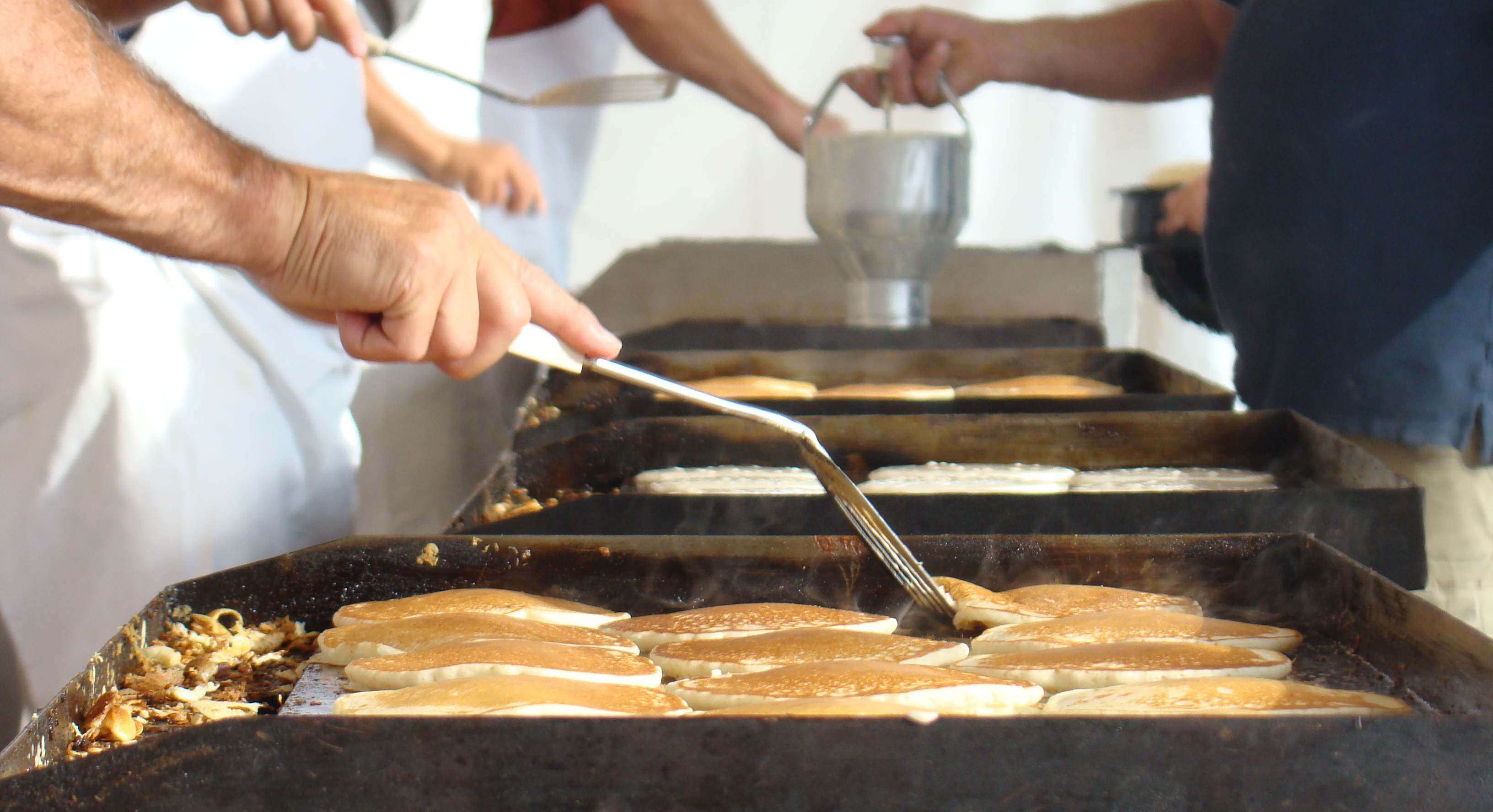 Flipping pancakes at the relief sale