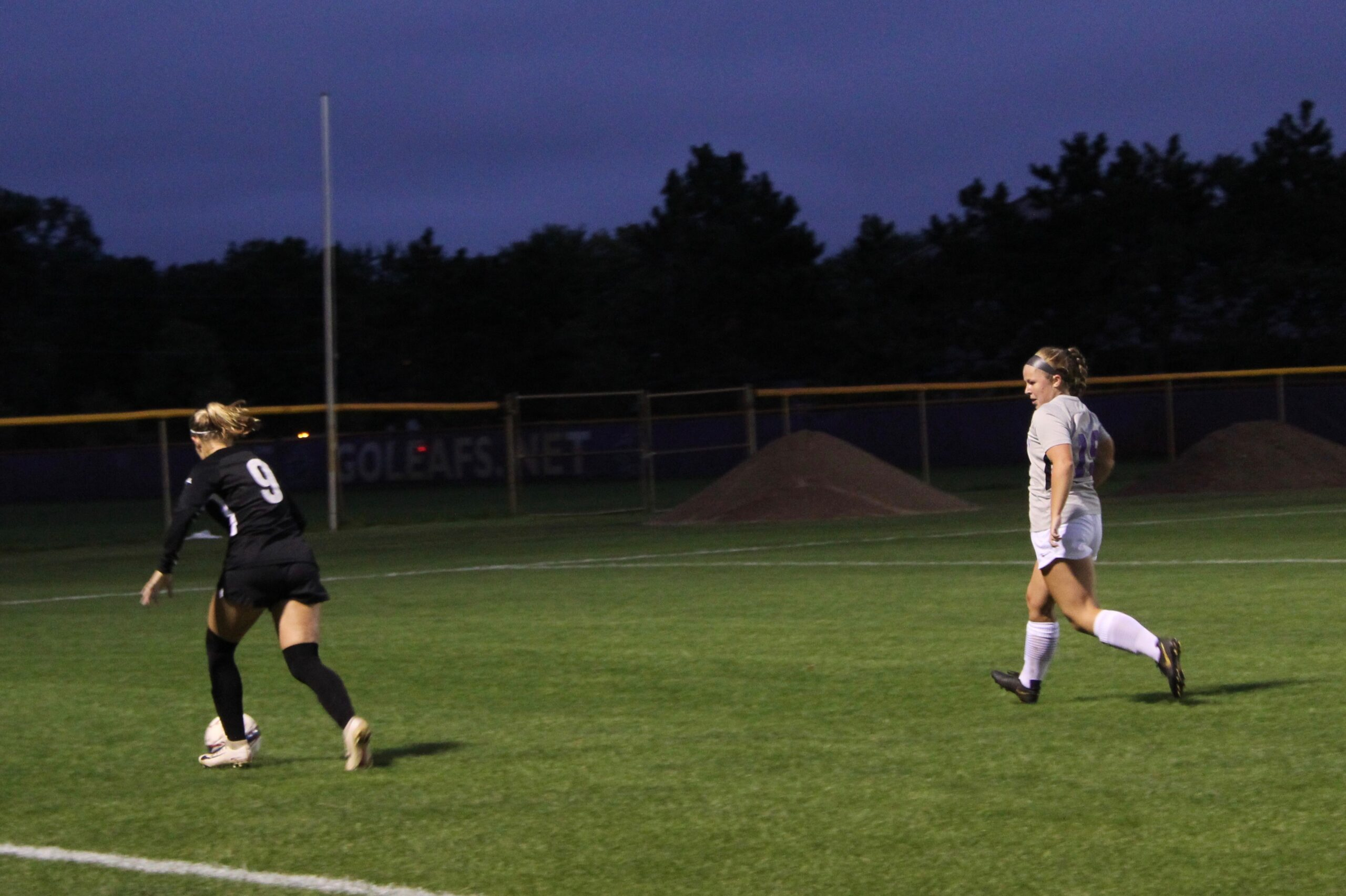 A Goshen women's soccer player and an opposing player run down the field during a game