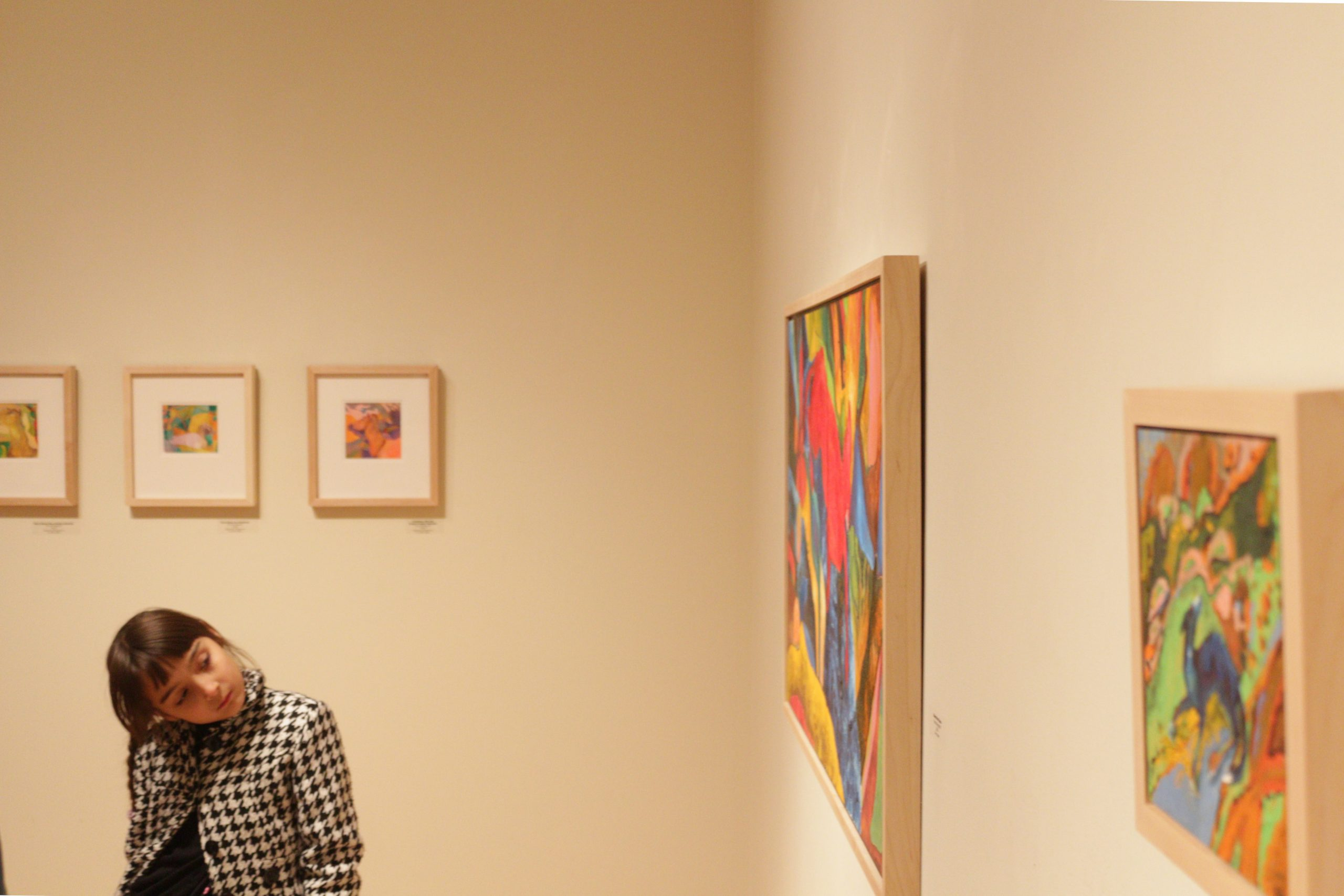 A student looks at the art hanging in the Hershberger Art Gallery