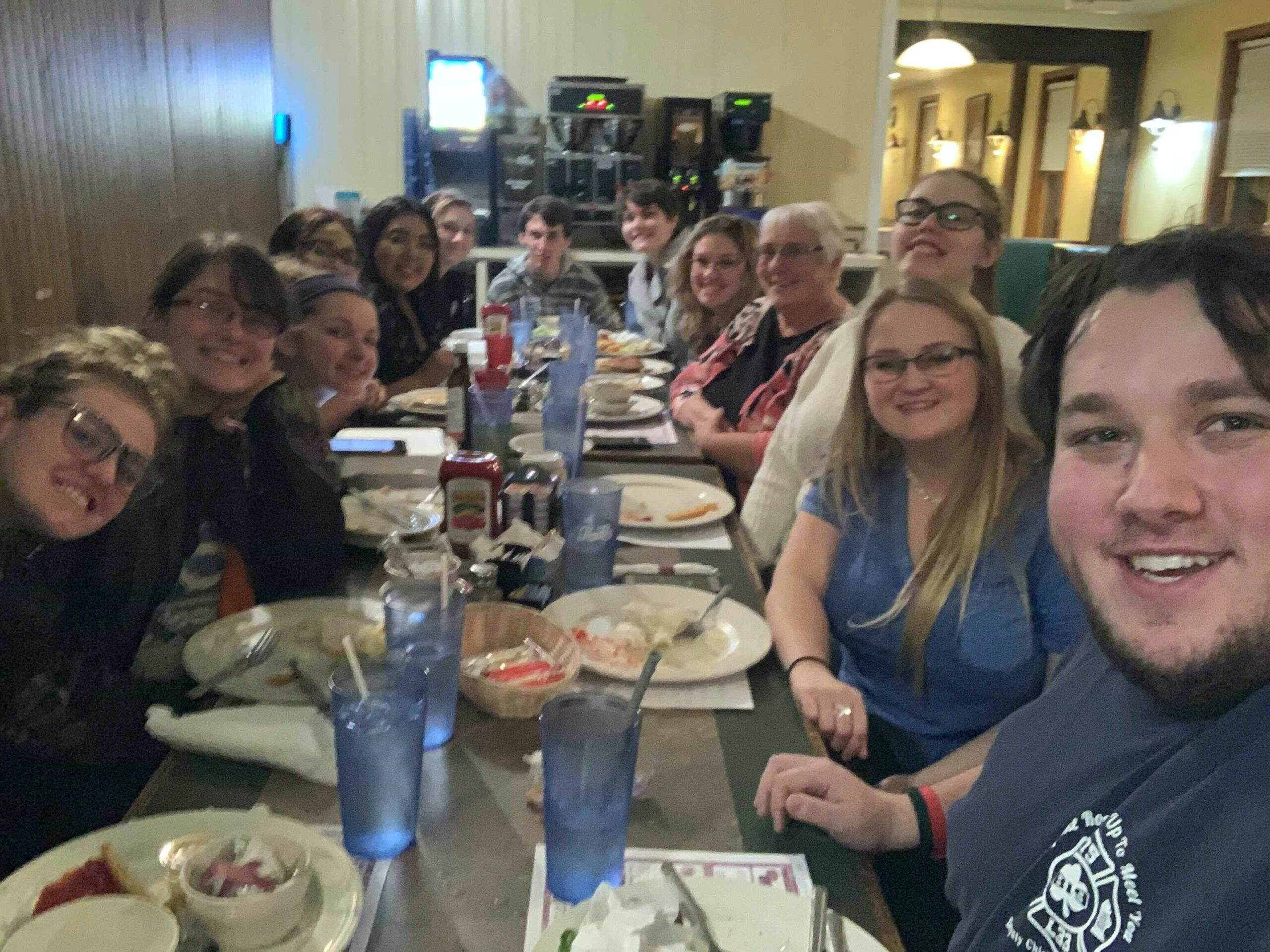 An interpreting major takes a selfie with other ASL majors at a restaurant dinner table