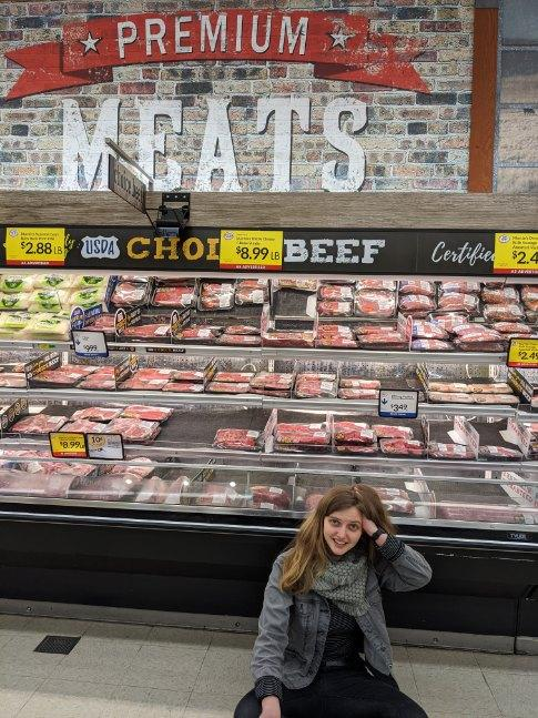 Greta Lapp Klassen sits in front of the premium meats section of the grocery store