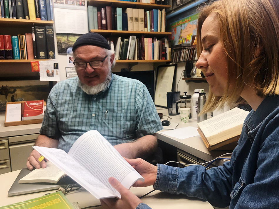 Paul Keim and a student sit in a book-filled office during an independent language study. The student is smiling at the book she is reading