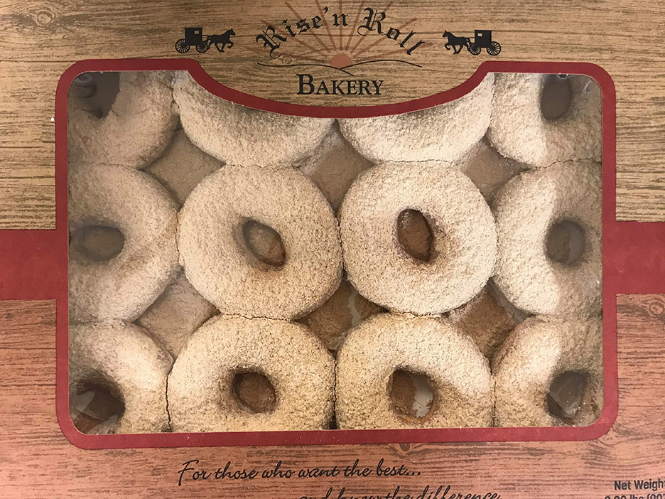 """A box of cinnamon caramel donuts or """"Amish crack."""" The box reads """"Rise'n Roll Bakery"""""""