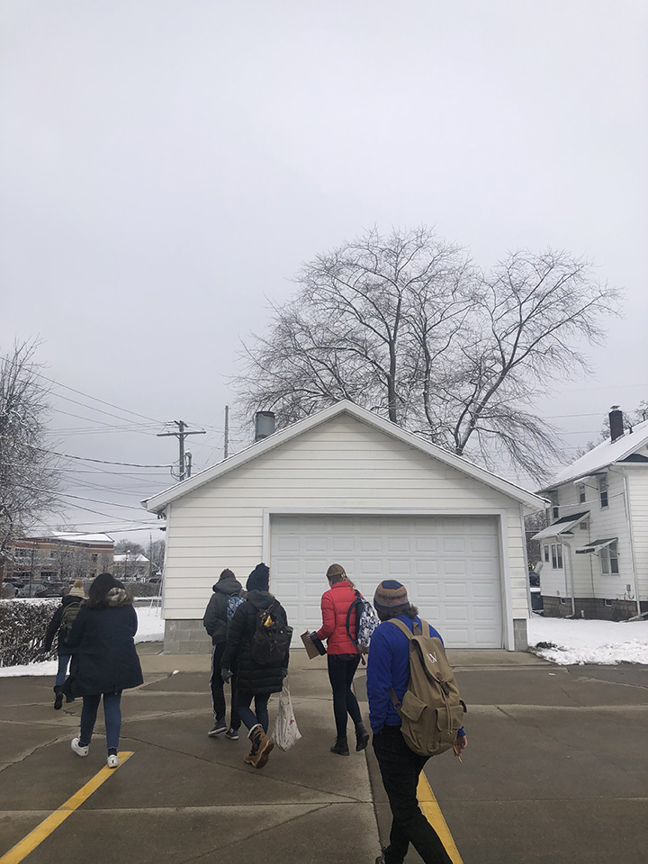 A group of students in winter coats and hats walk past the white garage of the Yoder-Culp Funeral Home