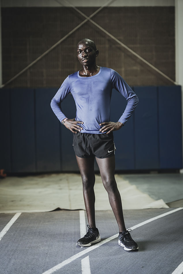 Victor Kiprop Kiprotich stands with his hands on his hips on the Goshen indoor track. He is wearing a long-sleeved purple shirt and black Nike running shorts
