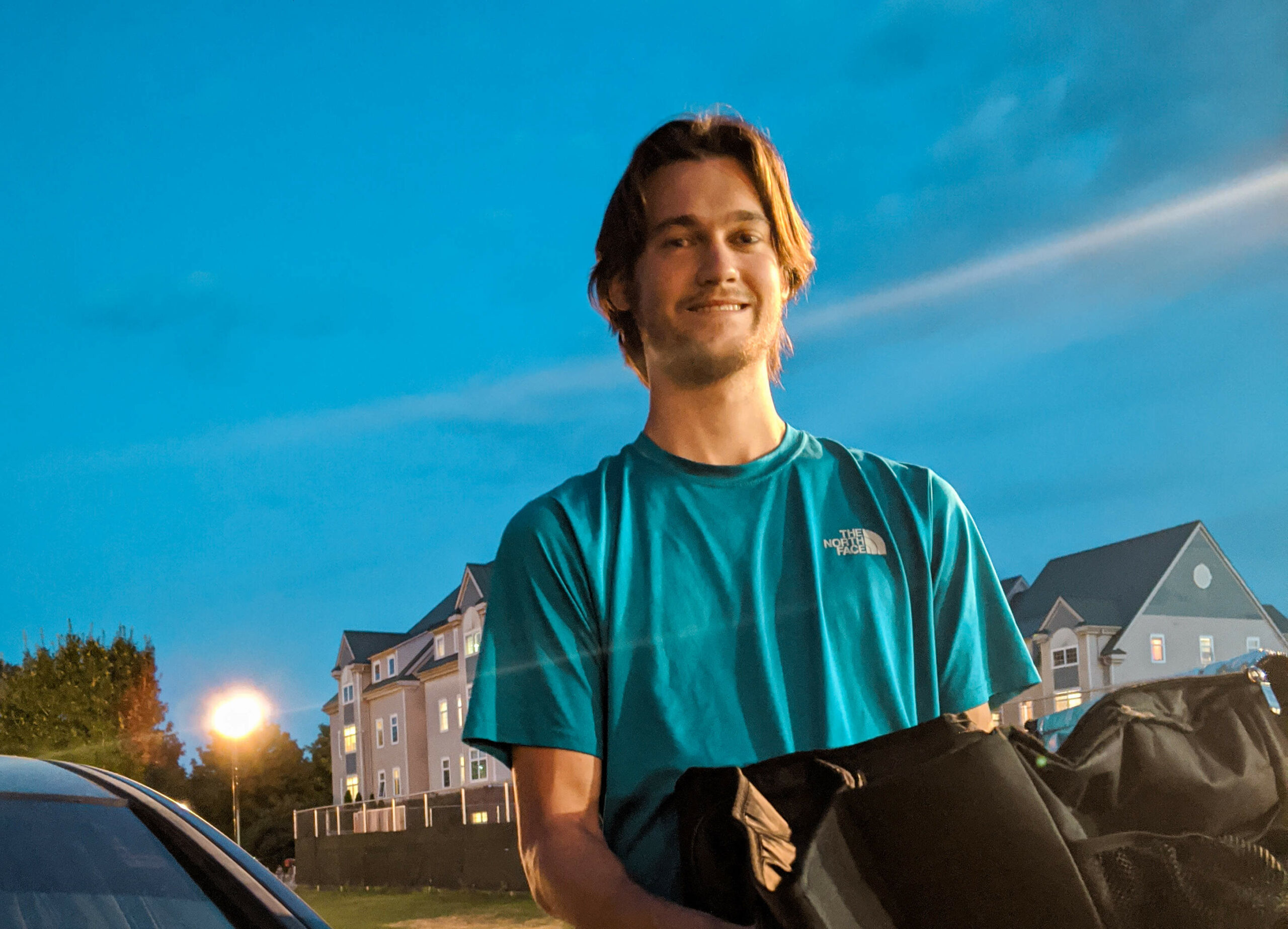 Simon Graber Miller stands next to his car and holds a bag of food that he is delivering through Grubhub and Door Dash