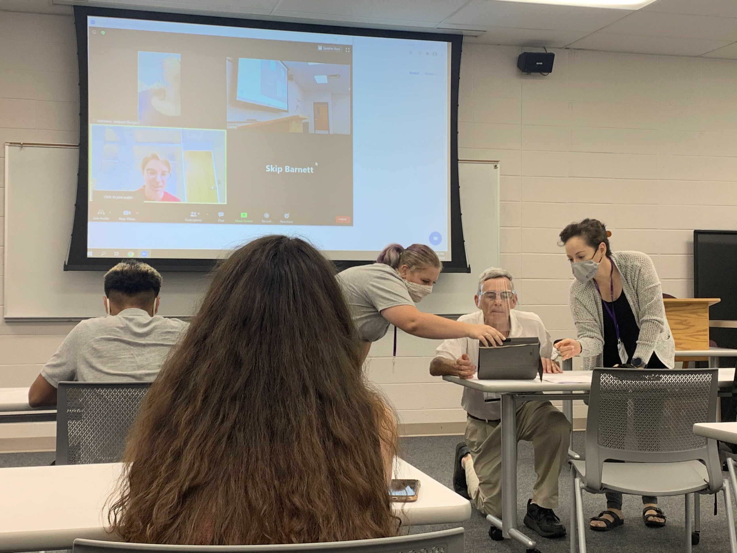 Skip Barnett is assisted by two masked students as he sets up a Zoom call with students who will be attending his class virtually. Skip is wearing a face shield. There are two other students in the classroom seated at desks, and the projector shows three students who are attending class virtually