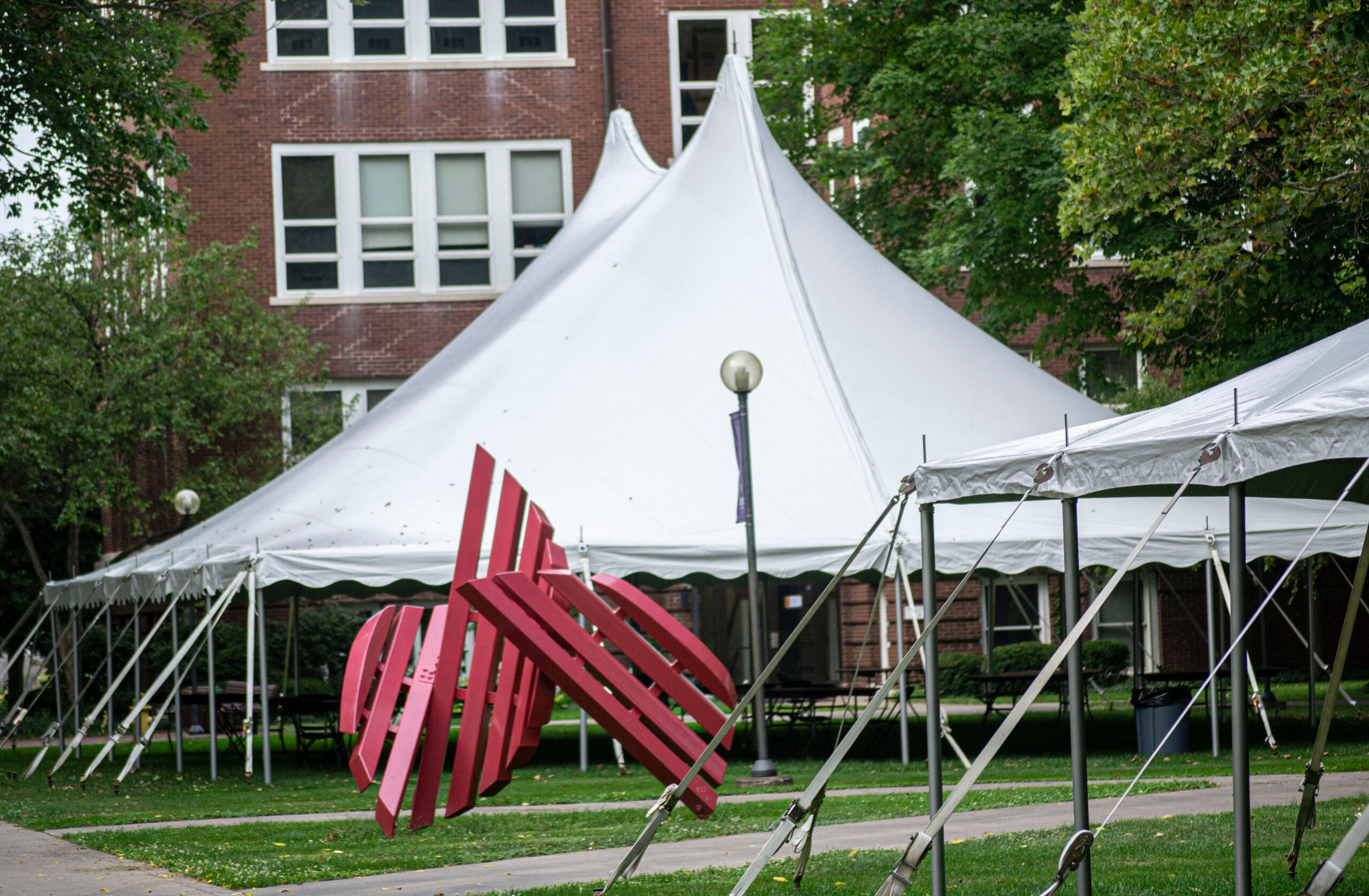 Photo of one of the on-campus tents next to the Broken Shield sculpture