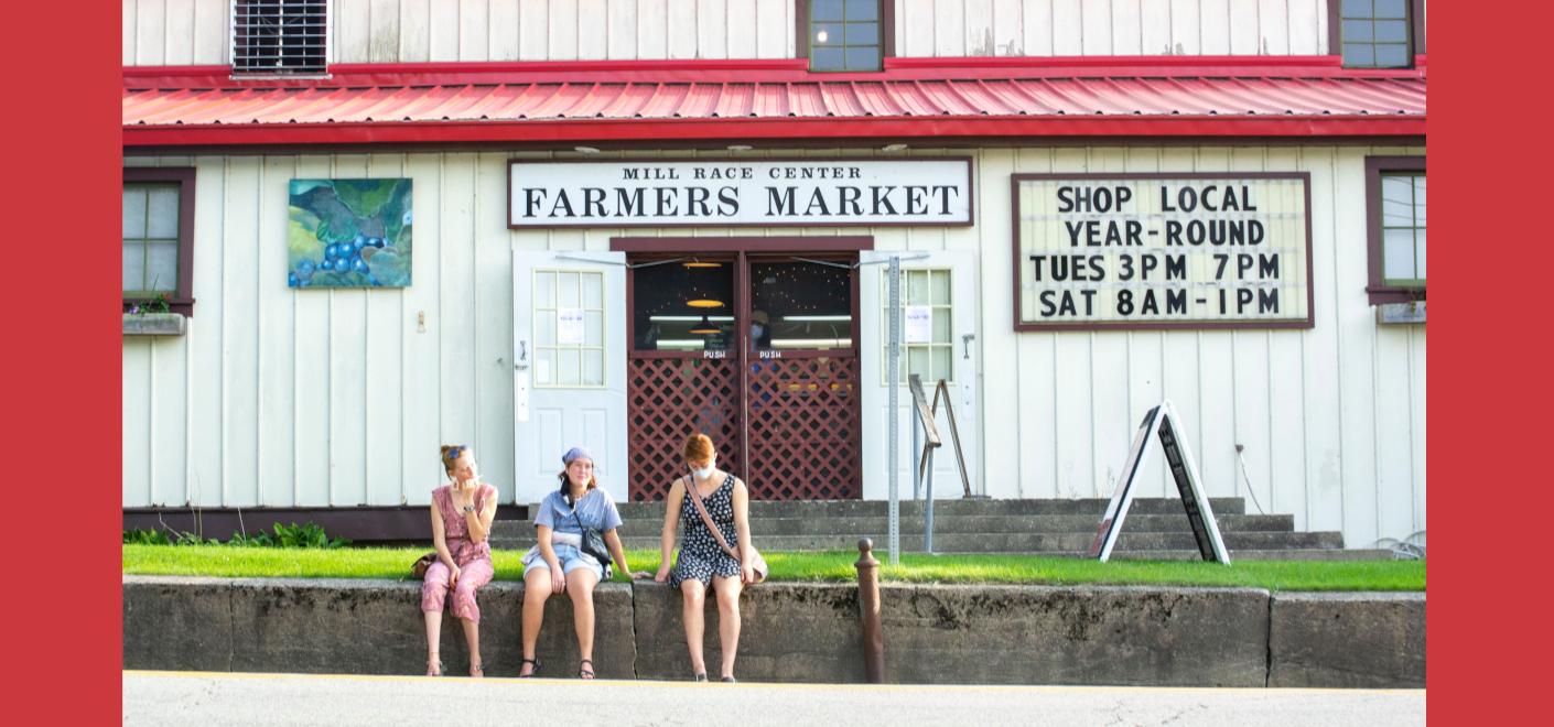 People sit outside the farmer's market