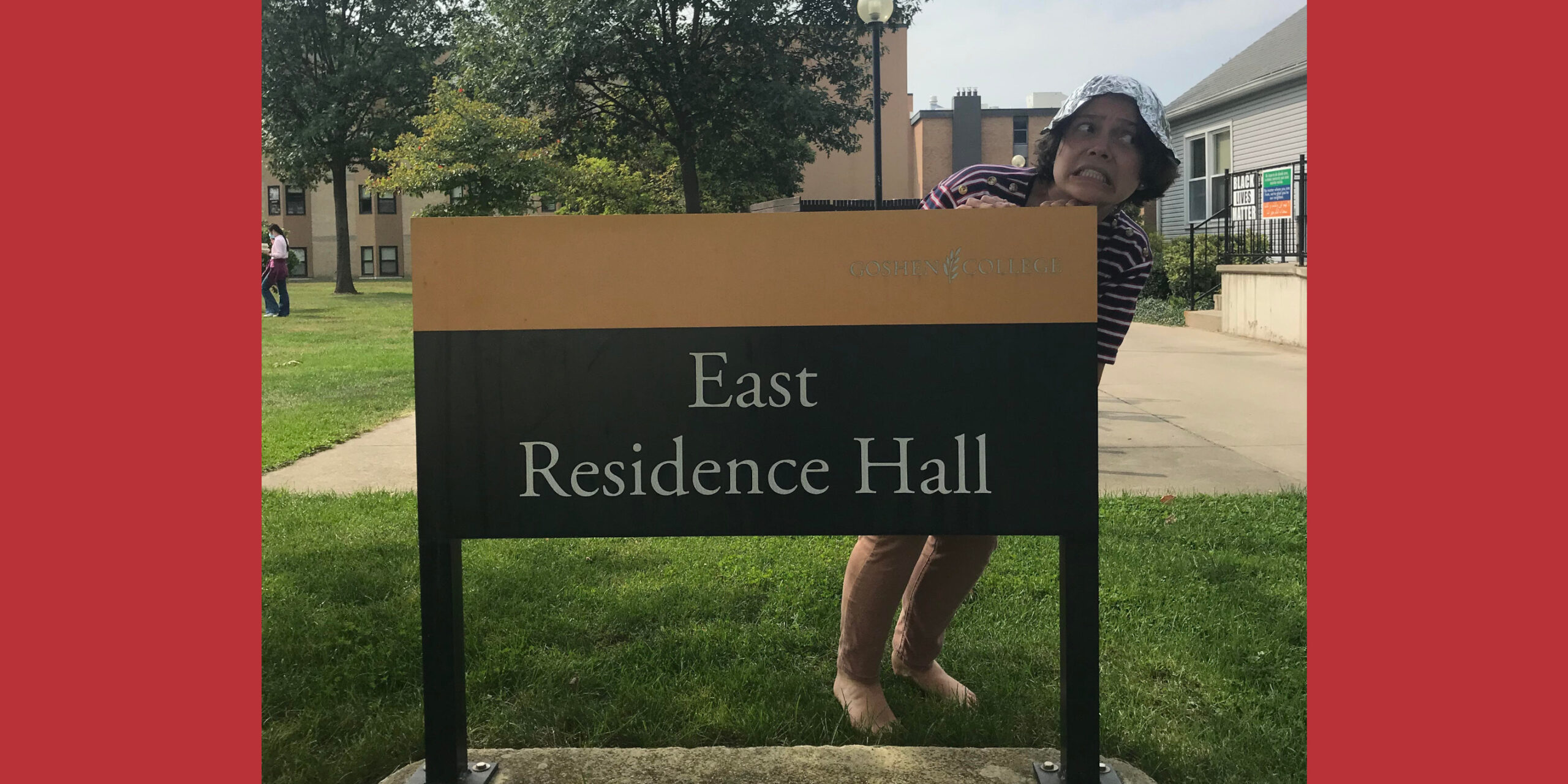 Kristin Jantzen makes a funny face behind the East Residence Hall sign