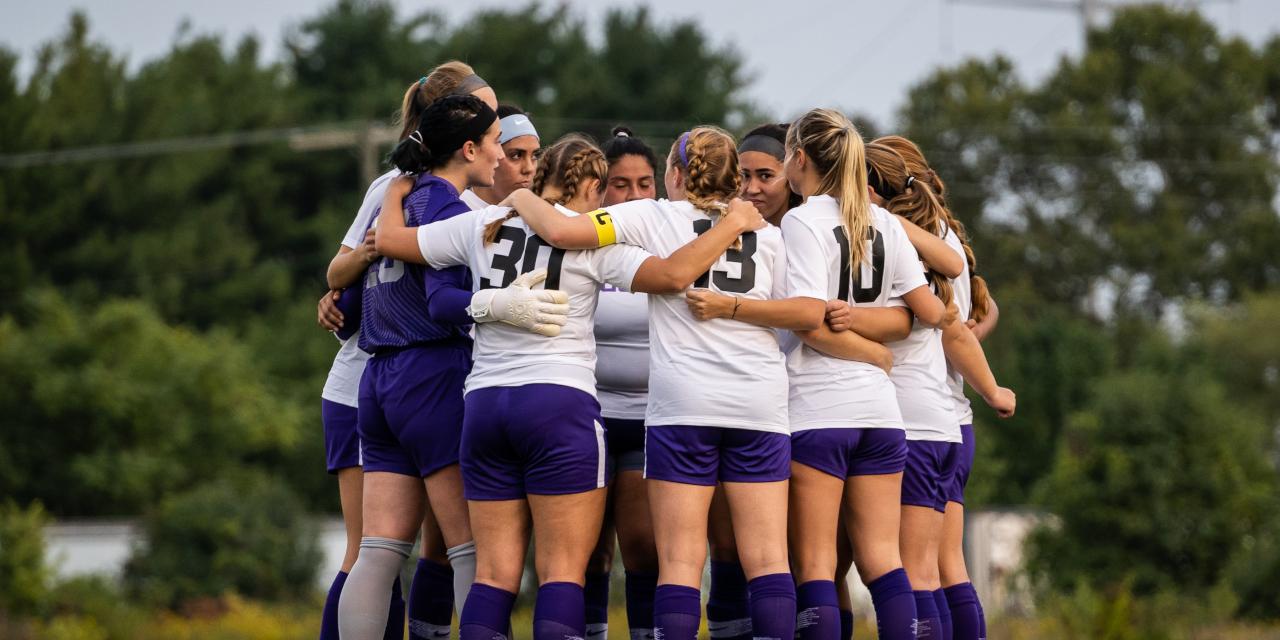 soccer team huddles together