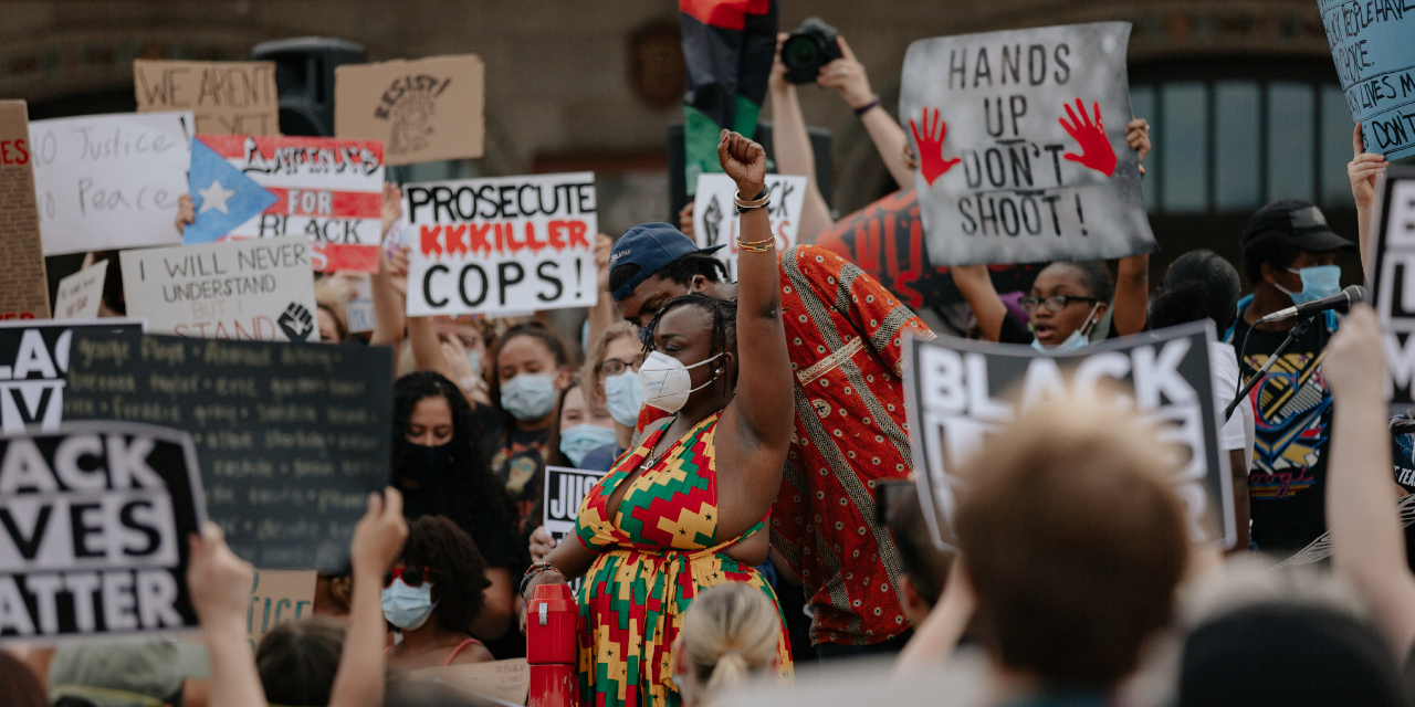 """A crowd of masked people hold up signs at a Black Lives Matter protest. The signs read """"Prosecute KKKiller Cops!"""" """"Hands Up Don't Shoot,"""" """"Black Lives Matter"""" and more. The people surround a Black woman in a brightly colored dress who is raising her fist in the air"""
