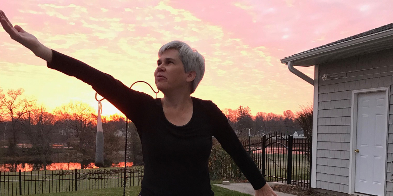 President Rebecca Stoltzfus stands with her right arm outstretched towards the sky, her palm pointing skyward. Her left arm is also outstretched, but pointing toward the ground. She is outdoors, and a sunrise can be seen in the background of the image