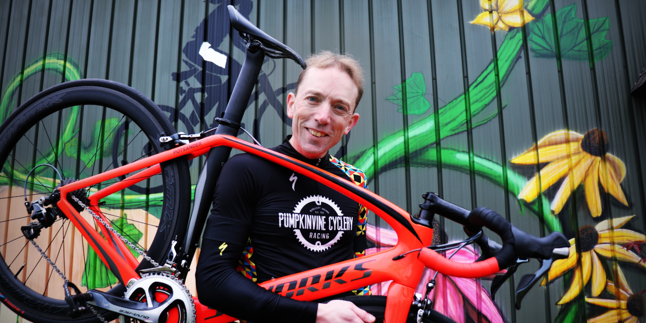 """Jason Potsander holds his bright red bike and smiles for the camera. He is wearing a black long-sleeved shirt reading """"Pumpkinvine Cyclery"""" and is standing in front of a flower mural"""
