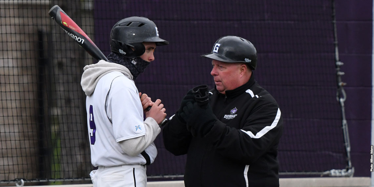 Doug Wellenreiter talks to a baseball player. Both are wearing Goshen College gear and Goshen batting helmets, and the student is holding a baseball bat