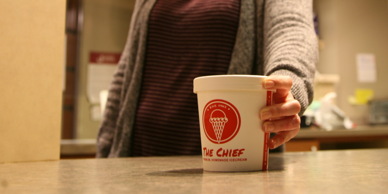 Close-up shot of a red and white pint of ice cream from the Chief. A student's hand holds the pint on the Java Junction counter