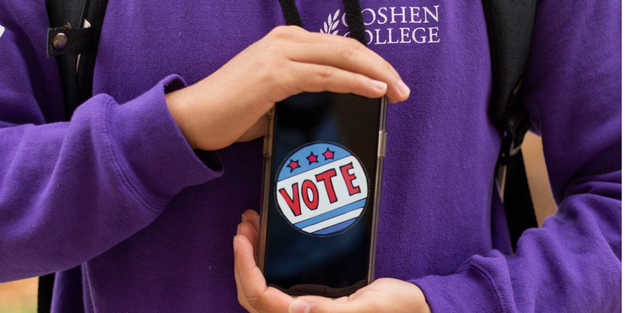 """Close-up shot of a student's hands holding up the red, white, and blue """"Vote"""" sticker on their phone screen. The student is wearing a purple """"Goshen College"""" shirt"""