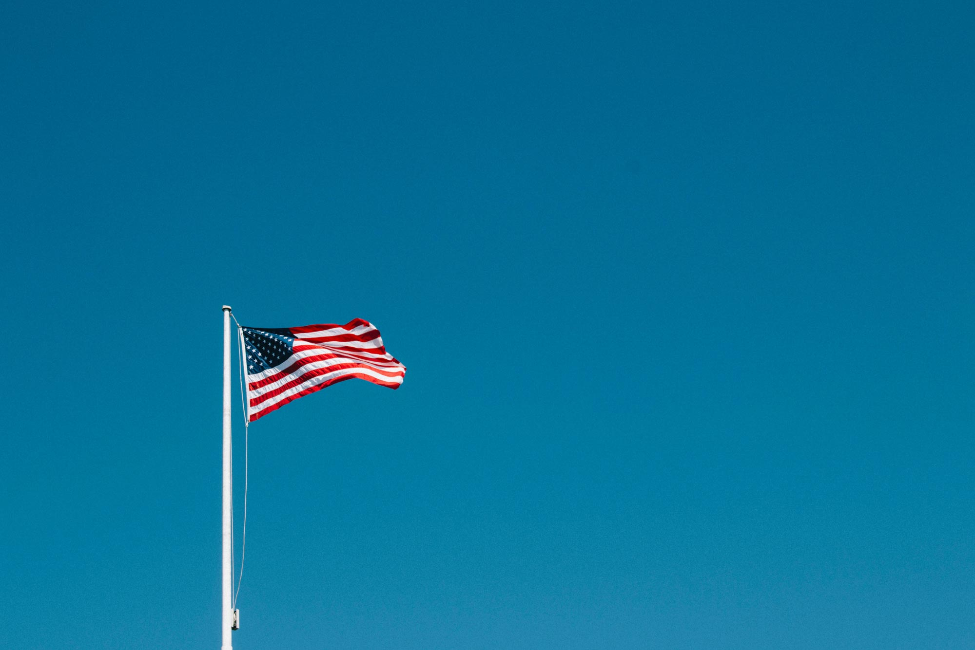 Photo of American flag with wide open blue sky in the background