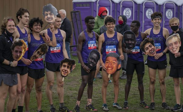Members of the men's cross country team hold cutout photos of their faces and laugh