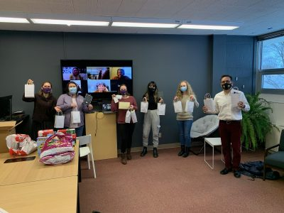 Members of the Student-Led Pandemic Task Force hold up care packages that they have prepared for quarantined and isolated students