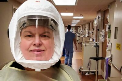 A hospital worker takes a selfie in protective gear