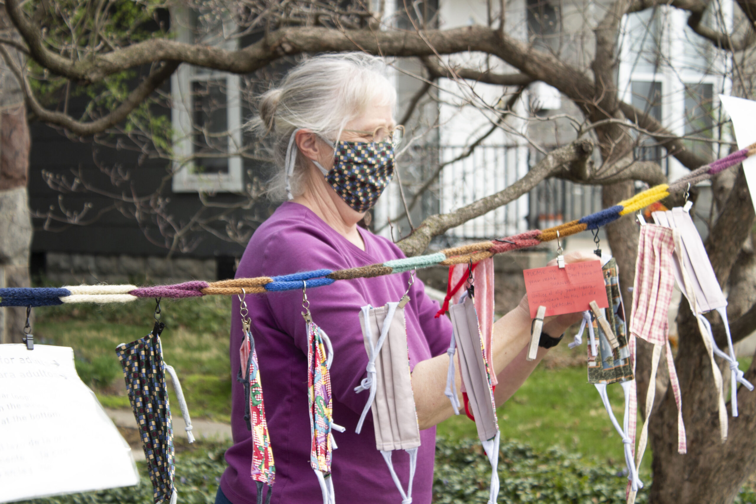 Barbara Gingerich hangs handmade masks on the communal clothesline outside her house