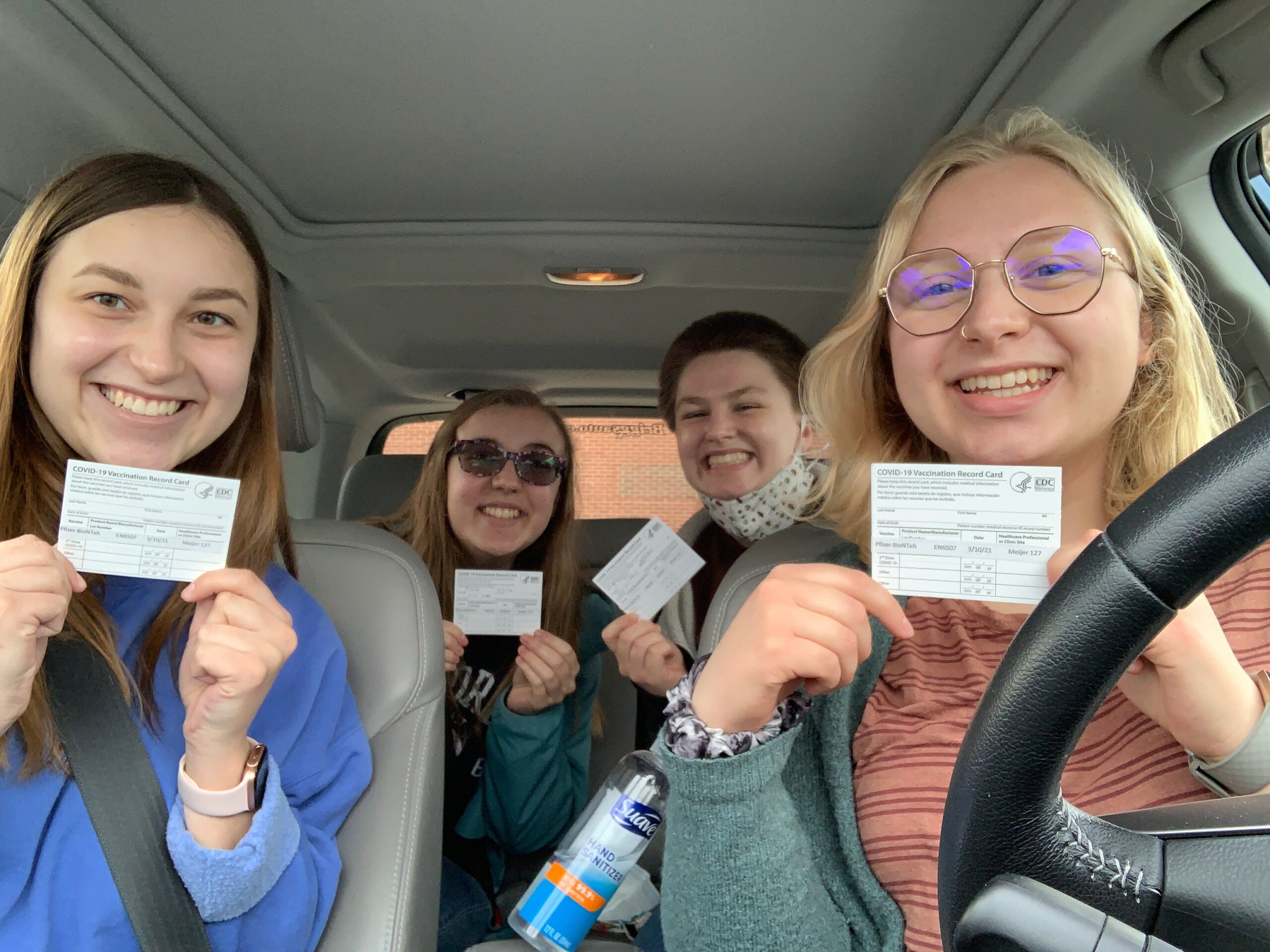 Students show off their new vaccination cards