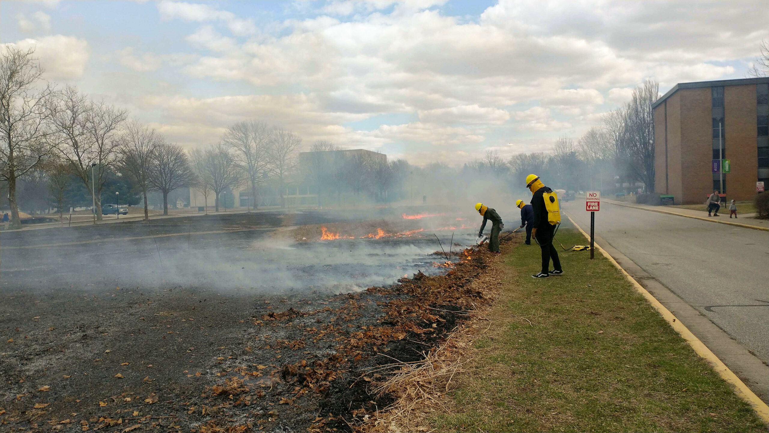 Students and staff wear protective gear as they monitor the Miller-Kratz prairie burning