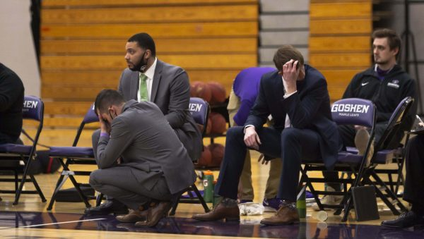 The men's basketball team coaches shake their heads in disappointment on the sidelines of a game