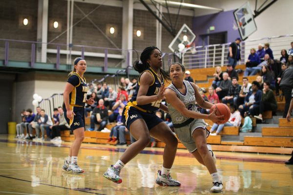 Mariah Roe fends off an opposing player as she approaches the basket for a shot