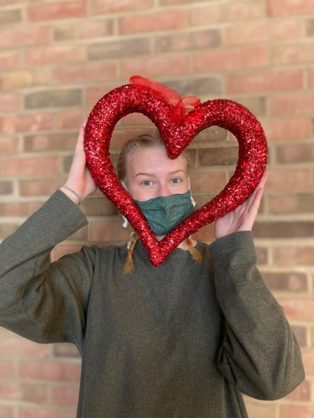 Anna Osborne poses for a picture with a heart-shaped picture frame